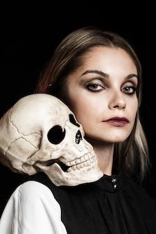 Mujer con cráneo humano en el hombro