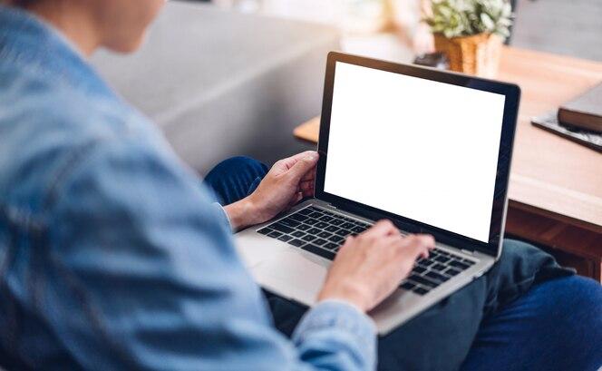 Mujer creativa joven que se relaja usando la computadora portátil que trabaja y que mecanografía en el teclado con las pantallas en blanco de la maqueta blanca en casa