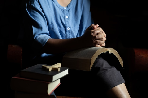 Mujer cristiana rezando en casa.