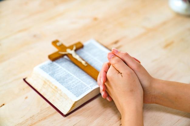 Mujer cristiana rezando con las manos cruzadas y la santa biblia a su lado