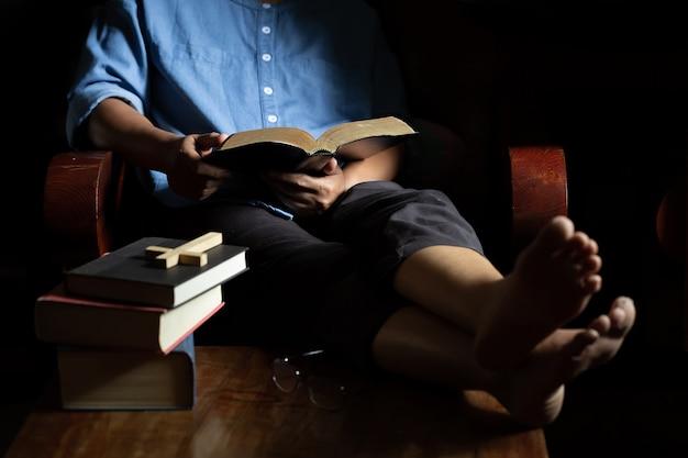 La mujer cristiana se sentó a leer la biblia en una silla de madera.