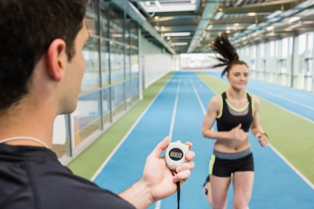 Mujer de cronometraje de entrenador en la pista