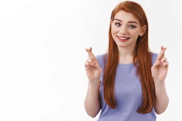 Mujer cruza los dedos para tener buena suerte mientras disfruta de obtener resultados positivos del trato. atractiva mujer pelirroja sonriente esperanzada pide un deseo, sueña que todo esté bien, anticipa el milagro, pared blanca