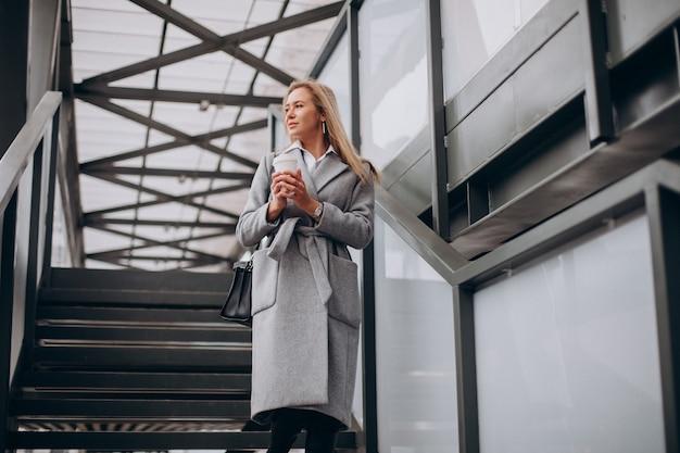 Mujer cruzando el puente y tomando café