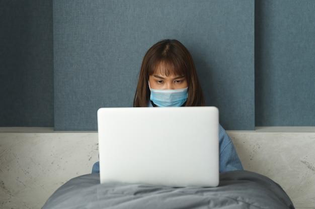Mujer en cuarentena por coronavirus con máscara protectora y trabajo inteligente
