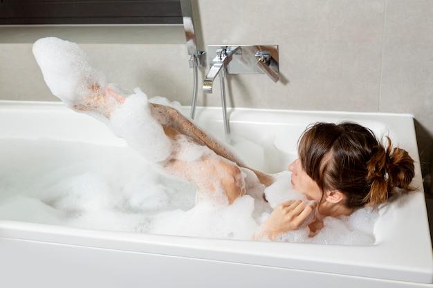 Mujer cubierta de espuma en la bañera.