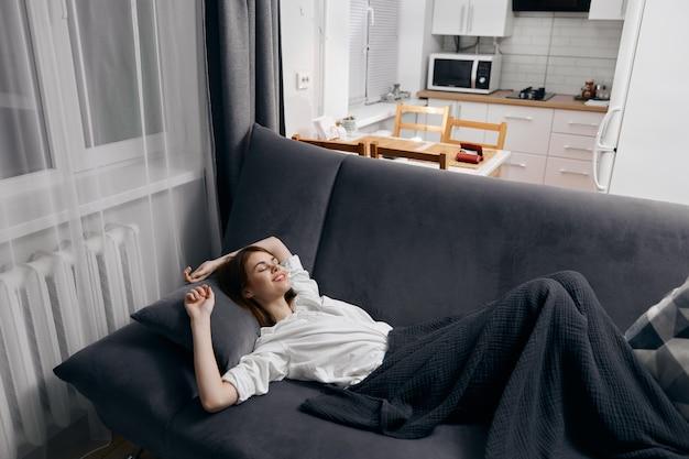 Mujer cubierta con una manta está acostada en el sofá y mirando hacia la ventana en el