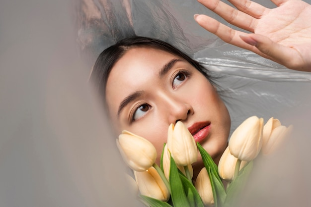 Mujer cubierta de plástico sosteniendo un ramo de flores