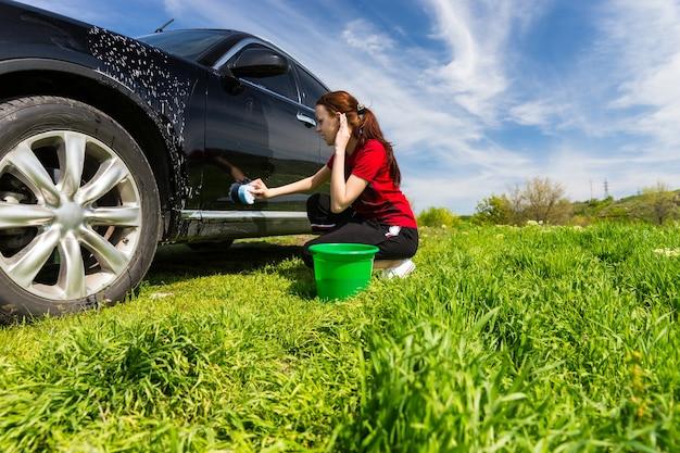 Mujer con cubo verde lavado negro vehículo de lujo con esponja jabonosa en campo de hierba verde en día soleado con cielo azul