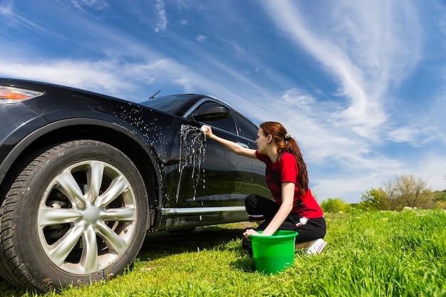 Mujer con cubo verde lavado de vehículo de lujo negro con esponja jabonosa en campo verde en día soleado con cielo azul