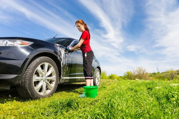 Mujer con cubo verde lavado de vehículos de lujo negro en campo con esponja jabonosa en día soleado