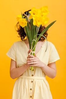 Mujer cubre la cara con flores