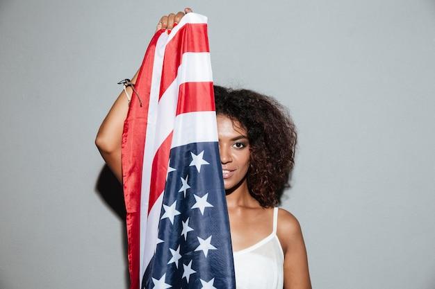 Mujer cubriendo la mitad de su rostro con la bandera de estados unidos