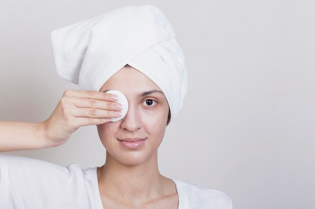 Mujer cubriendo un ojo con disco de maquillaje