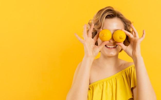 Mujer cubriendo los ojos con limones