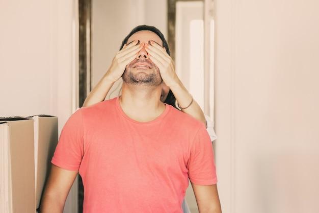 Mujer cubriendo los ojos de su novio con las manos y llevándolo a su nuevo apartamento con cajas de cartón