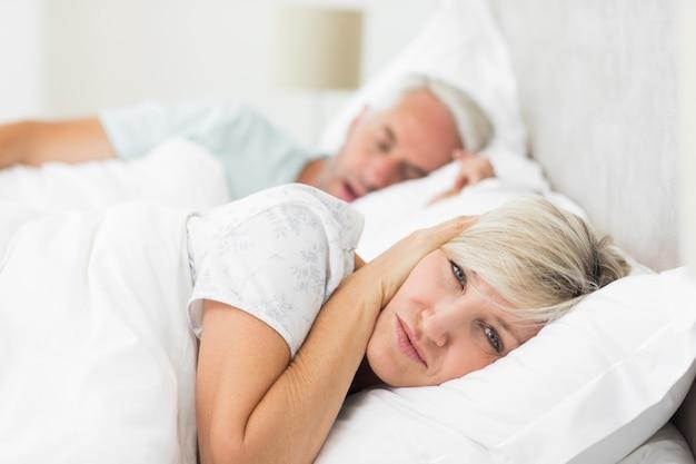 Mujer cubriendo las orejas mientras el hombre ronca en la cama