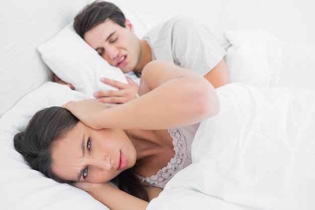 Mujer cubriendo las orejas mientras su pareja está roncando
