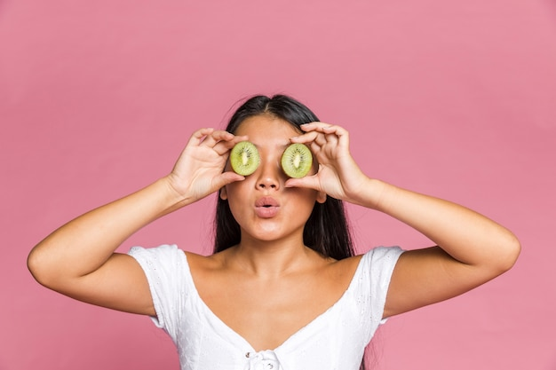 Mujer cubriendo sus ojos con kiwi en superficie rosa