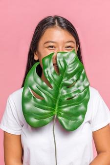 Mujer cubriéndose la cara con hojas de monstera
