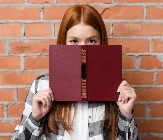 Mujer cubriéndose la cara con el libro