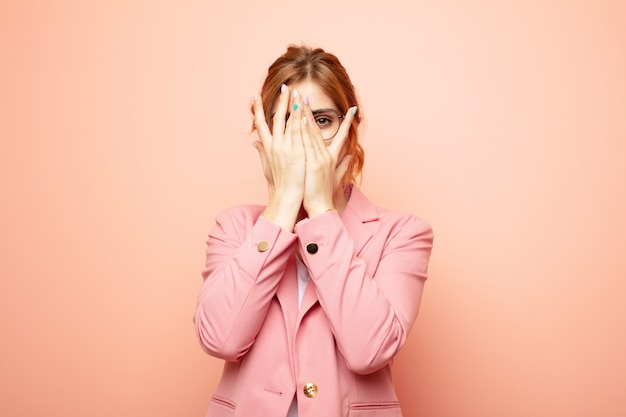 Mujer cubriéndose la cara con las manos, mirando entre los dedos con expresión sorprendida y mirando a un lado