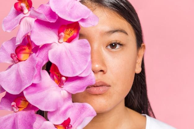 Mujer cubriéndose la cara con pétalos de orquídea