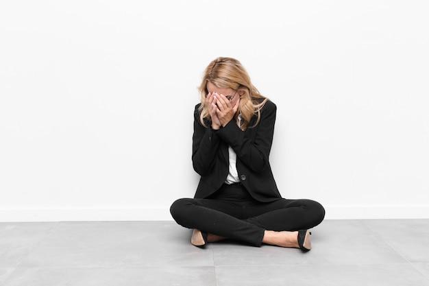 Mujer cubriéndose los ojos con las manos con una mirada triste y frustrada de desesperación, llorando, vista lateral