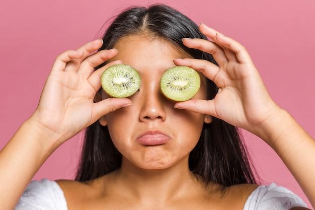 Mujer cubriéndose los ojos con mitades de kiwi