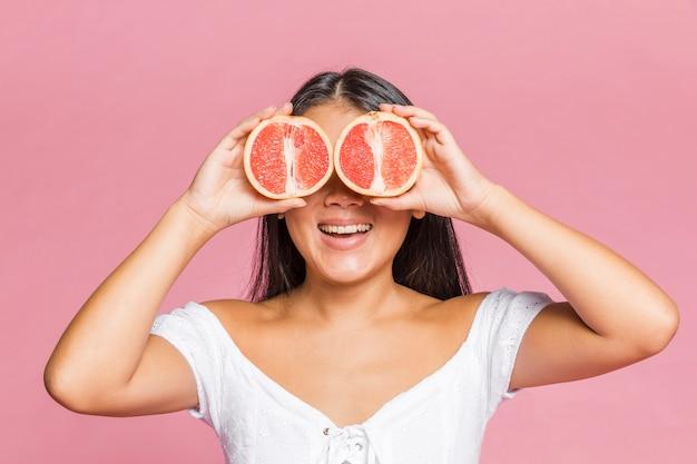 Mujer cubriéndose los ojos con mitades de toronja
