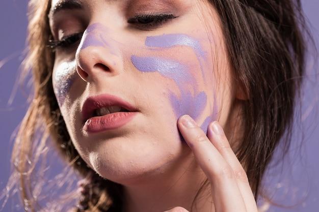 Mujer cubriéndose con pintura como señal de triunfo