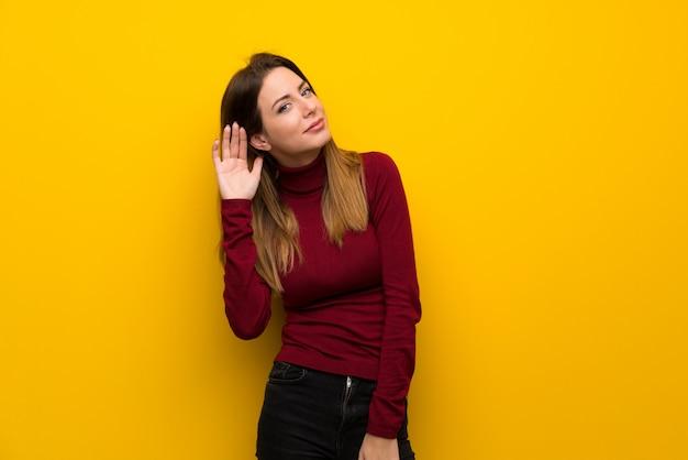 Mujer con cuello alto sobre una pared amarilla escuchando algo poniendo la mano en la oreja