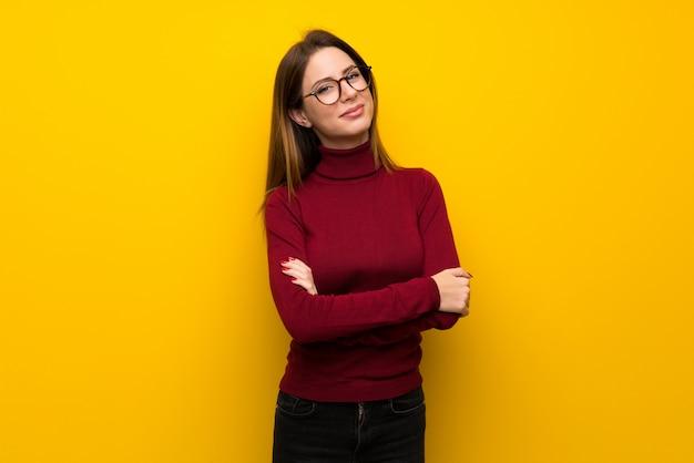 Mujer con cuello alto sobre pared amarilla con gafas y feliz