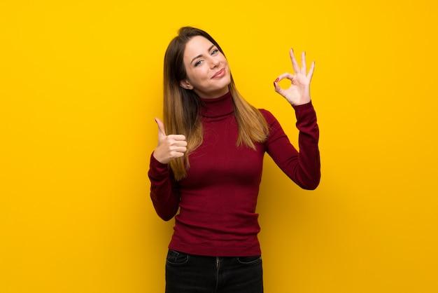 Mujer con cuello alto sobre una pared amarilla que muestra el signo correcto con y dando un pulgar hacia arriba gesto