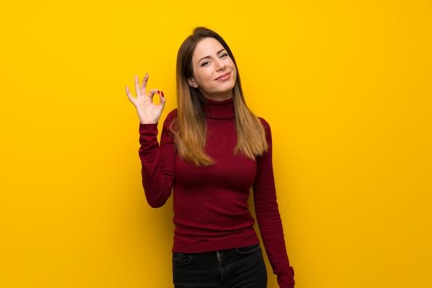 Mujer con cuello alto sobre una pared amarilla que muestra el signo correcto con los dedos
