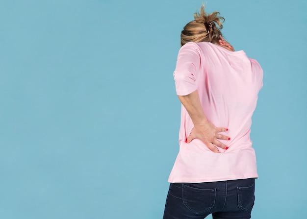 Mujer con cuello y dolor de espalda de pie frente a fondo azul