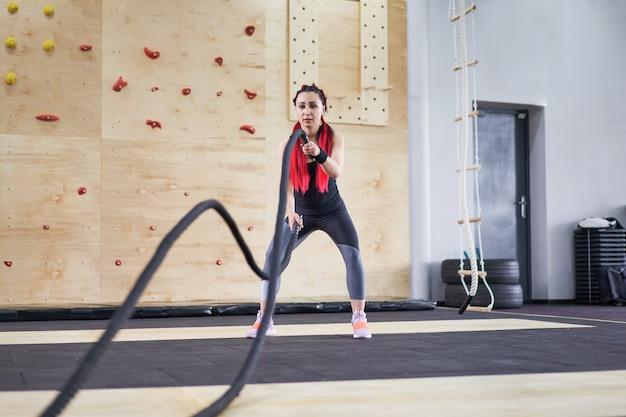 Mujer de cuerda de batalla de gimnasio