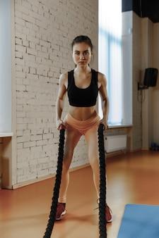 Mujer con cuerdas de batalla ejercicio en el gimnasio. atleta, deporte, cuerda, entrenamiento, entrenamiento, ejercicios y concepto de estilo de vida saludable