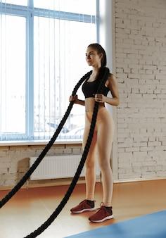 Mujer con cuerdas de batalla ejercicio en el gimnasio
