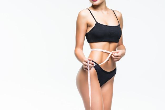 Mujer de cuerpo femenino con cinta de centímetro alrededor en la pared blanca.