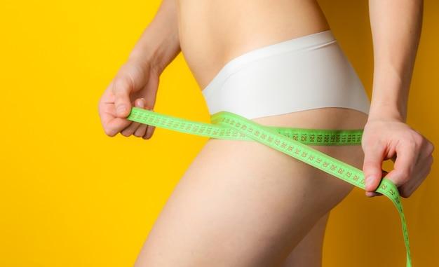 Una mujer con un cuerpo perfecto en bragas mide sus caderas con una regla en amarillo