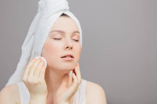 La mujer cuida su rostro, después de una ducha con una toalla sobre un gris, un algodón en la mano