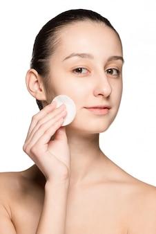 Mujer del cuidado de la piel que quita la cara con un algodón