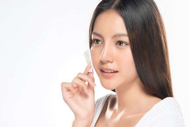 Mujer del cuidado de la piel que quita el maquillaje de la cara con un algodón.