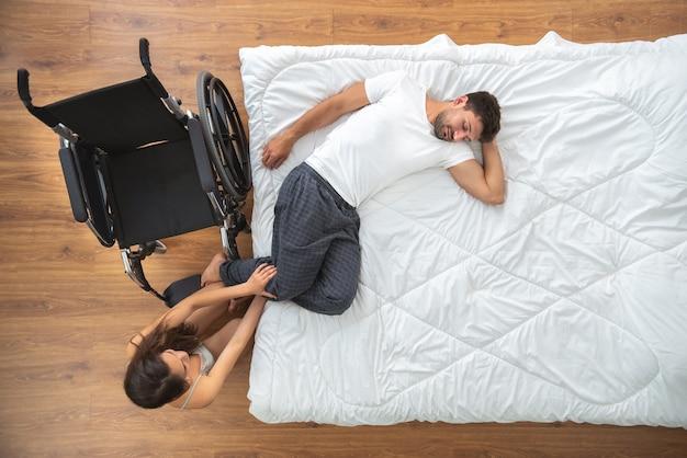 La mujer cuidando a un hombre discapacitado en la cama. vista desde arriba
