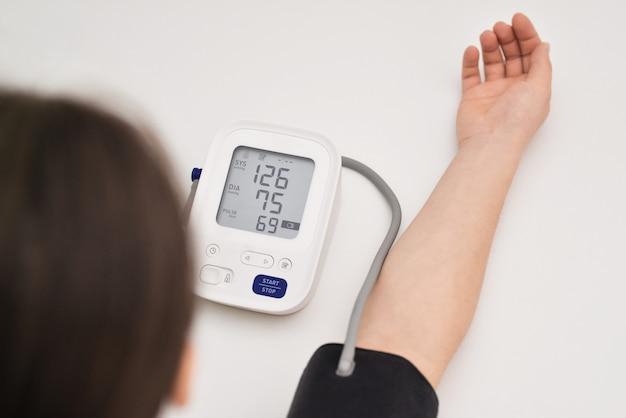 La mujer está cuidando la salud con monitor de latidos cardíacos y presión arterial