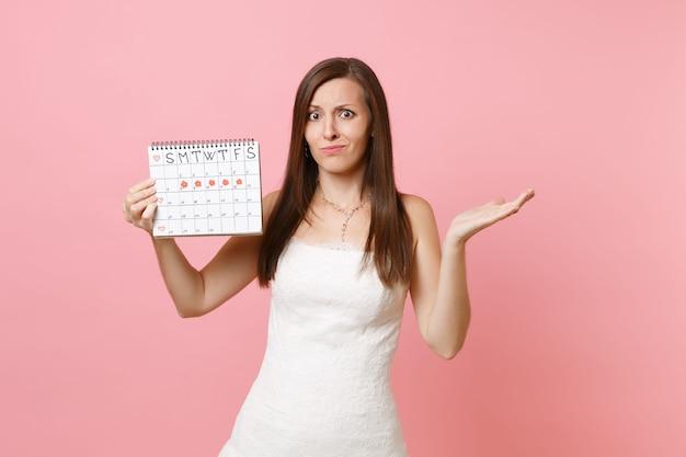 Mujer culpable desconcertada en vestido blanco extendido mano mantenga calendario de períodos femeninos para comprobar los días de menstruación