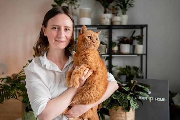 Mujer cultivando plantas en casa con gato