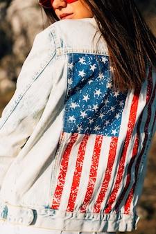 Mujer de cultivo en chaqueta vaquera con bandera americana.