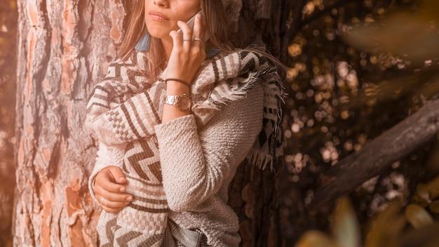 Mujer de cultivo hablando en el teléfono inteligente cerca de un árbol